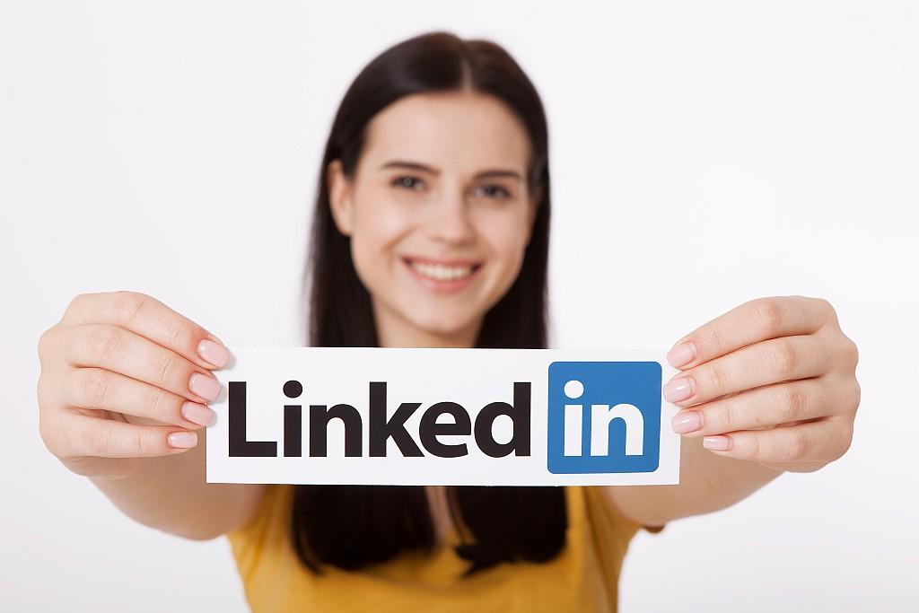 девушка держит в руках лого Linkedin